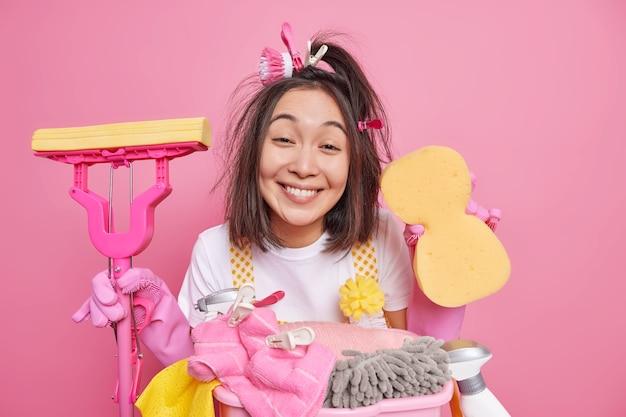 검은 머리카락을 가진 긍정적 인 주부의 실내 촬영은 스폰지를 보유하고 걸레는 청소 도구를 사용하여 분홍색 backgound 위에 고립 된 세탁 바구니 근처에 서서 집을 가져옵니다. 집안일 개념