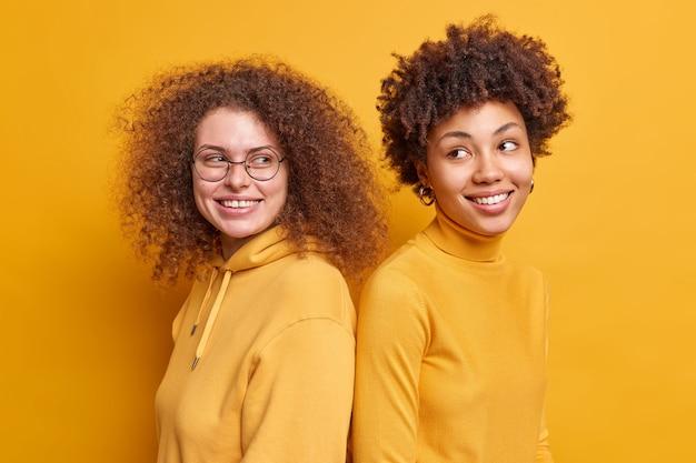 긍정적 인 다민족 여성의 실내 샷은 어깨를 나란히 서서 즐겁게 옷을 입고 웃으며 노란색 벽 위에 고립 된 좋은 분위기의 곱슬 머리를 가지고 있습니다. 다양한 행복한 친구