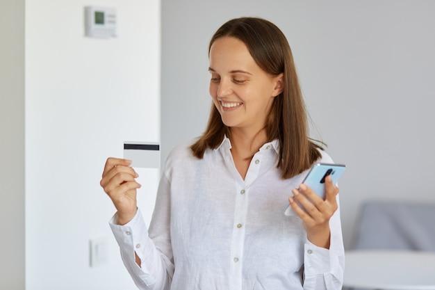 Крытый снимок положительной довольной женщины в белой рубашке, стоящей дома, позирующей со смартфоном в руке, показывающей кредитную карту с большой суммой денег на счету.