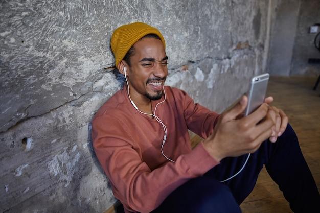 Снимок в помещении: позитивно улыбающийся молодой бородатый мужчина с темной кожей сидит на деревянном полу и держит мобильный телефон в руках, хмурится и демонстрирует свои идеальные белые зубы