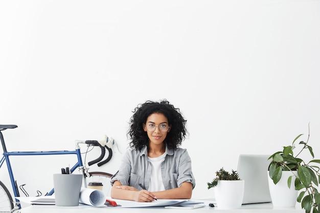 オフィスデスクに座っている肯定的な笑顔の若い浅黒い女性のインテリアデザインの室内撮影