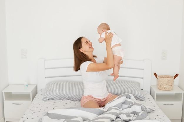 밝은 방에서 침대에 앉아 어린 아기와 놀고 있는 긍정적인 미소를 짓고 있는 젊은 어머니의 실내 사진, 흰색 캐주얼 스타일의 티셔츠와 분홍색 반바지를 입은 여성, 행복한 어머니.