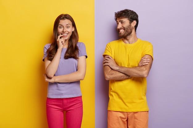 긍정적 인 젊은 여성과 남성의 실내 촬영은 행복하게 미소 짓고 기분이 좋으며 함께 자유 시간을 보내고 티셔츠를 입습니다.
