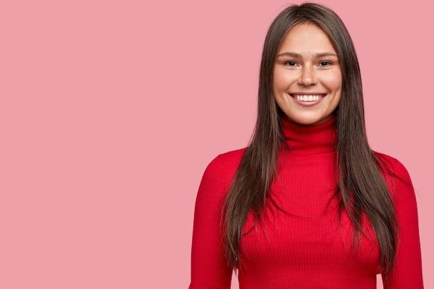 Снимок в помещении: симпатичная темноволосая девушка, одетая в повседневный красный свитер с высоким воротом, со свободным пространством справа.