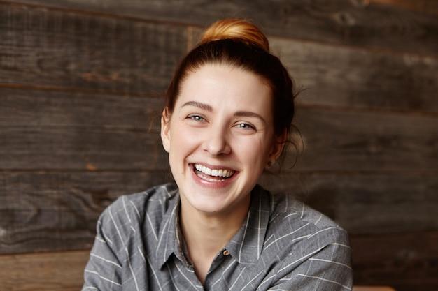 きれいな肌とコーヒーショップで楽しんで完璧な笑顔でかわいい女の子の屋内撮影