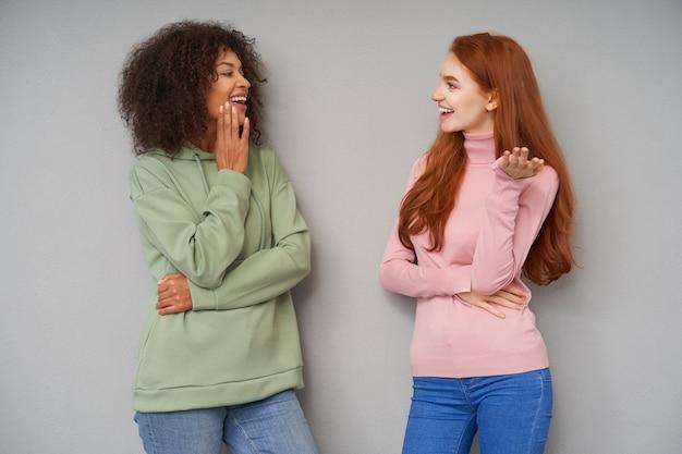 Крытый снимок довольно счастливых дам, одетых в повседневную одежду, которые смотрят друг на друга, весело разговаривают и весело улыбаются, изолированные на серой стене