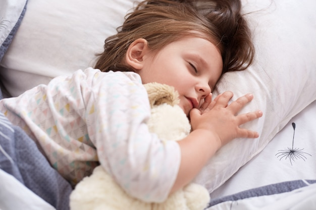 自宅のベッドで寝ている間に白い柔らかい犬のおもちゃを抱いてかわいい女の子の屋内撮影