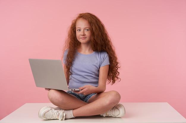 파란색 티셔츠와 청바지 반바지를 입고 분홍색 배경 위에 다리를 건너 앉아 매력적인 미소로 카메라를보고 긴 곱슬 머리를 가진 예쁜 빨간 머리 소녀의 실내 촬영