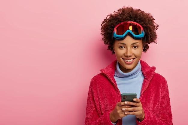 예쁜 스키어 여자의 실내 촬영은 스마트 폰 장치를 사용하고, 스키 마스크를 쓰고, 카메라에 행복하게 미소 짓고, 분홍색 스튜디오 벽 위에 절연되어 있습니다.