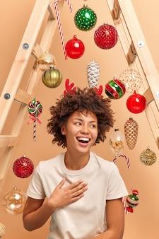 곱슬 아프리카 머리를 가진 꽤 웃는 젊은 여자의 실내 촬영은 행복하게 웃고 옆으로 보이는 빨간 뿔 캐주얼 흰색 티셔츠를 입고 겨울 방학이 집에서 크리스마스를 준비합니다.