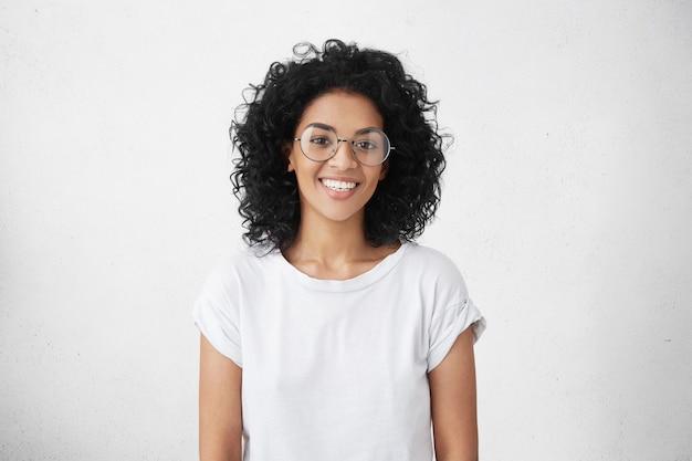 かわいい広い笑顔でかなり学生の女の子の屋内撮影