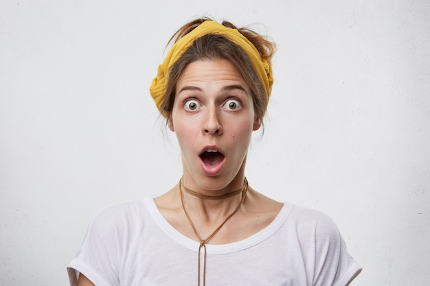 Снимок в помещении: симпатичная женщина смотрит с потрепанными глазами и отвисшей челюстью в желтом шарфе на голове, кулоне и белой повседневной футболке с удивленным выражением лица.