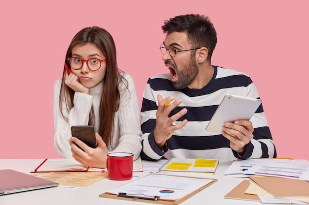 Снимок в помещении: красивая женщина в очках сидит рядом со своим наставником, который сердито кричит