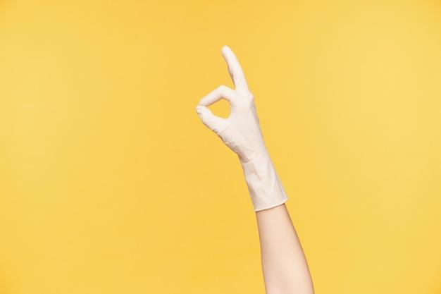 고무 흰 장갑에 제기 된 여성의 손의 실내 샷은 손가락으로 잘 된 제스처를 형성하고, 봄 청소를 마무리하고 만족하며, 오렌지 배경 위에 포즈를 취합니다.