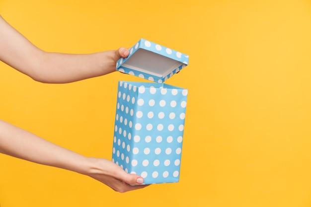 黄色の背景の上にポーズをとっている間、かわいい女性の手で保持されている長方形のミント点線の紙箱の屋内ショット。工芸品とholdaysの概念