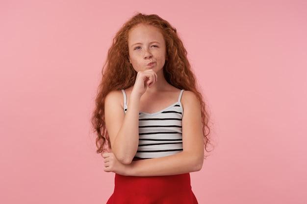 Снимок в помещении: рыжая кудрявая девочка с непринужденной прической в красной юбке и полосатом топе держит подбородок поднятой рукой и задумчиво смотрит в камеру, изолирована на розовом фоне