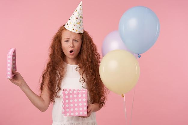 Снимок в помещении: рыжая девушка с вьющимися волосами в белом платье и шапочке для дня рождения стоит на розовом фоне студии, смотрит в камеру с расстроенным лицом и хмурится, держа подарочную коробку в руках