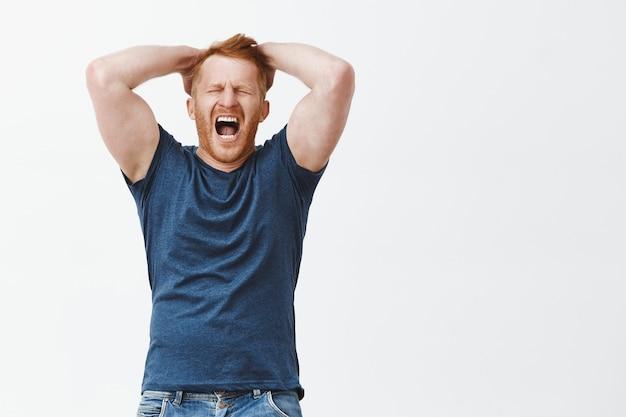 Снимок в помещении: рыжий мужчина испытывает страдание и болезненные эмоции, держит руки за голову, кричит или кричит с закрытыми глазами