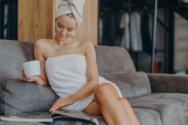Снимок в помещении: расслабленная красивая женщина расслабленно сидит на диване, носит банное полотенце вокруг тела после душа, держит чашку чая, читает журнал, проводит свободное время дома. оздоровление, концепция гигиены
