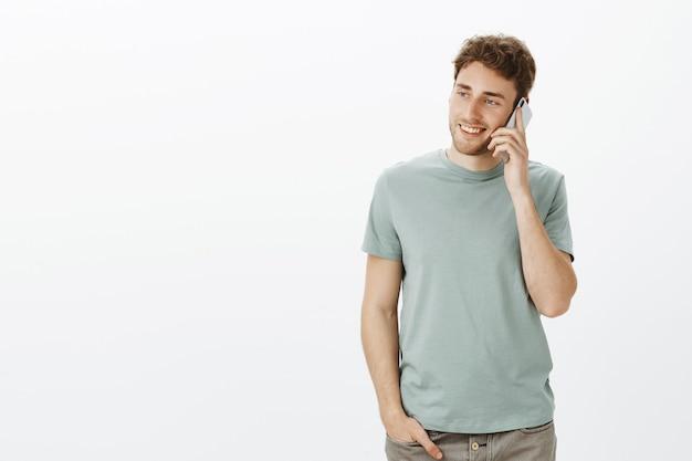 Снимок в помещении: расслабленный очаровательный европейский мужчина со светлыми волосами, держащий смартфон возле уха и смотрящий влево с широкой улыбкой, небрежно разговаривает с сестрой