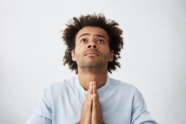 Tousled 머리를 가진 종교적 절망적 인 젊은 아프리카 계 미국인 남자의 실내 촬영