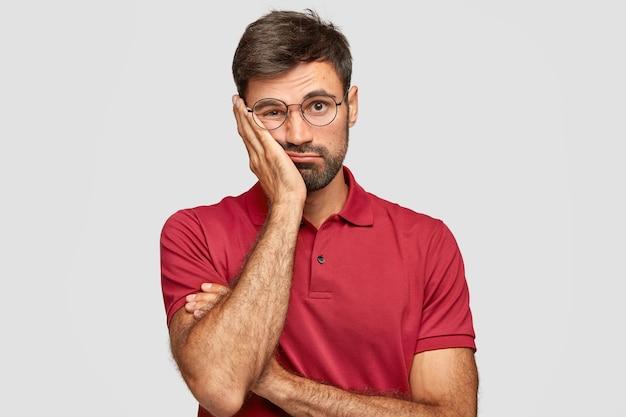슬픈 남자의 실내 촬영은 지루해 보이며 뺨에 손을 유지합니다.