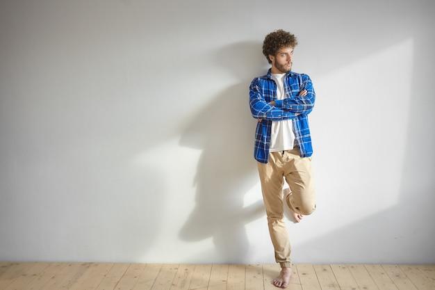 Снимок в помещении: грустный и угрюмый молодой небритый мужчина, одетый в повседневную одежду, позирует босиком, скрестив руки на груди, чувствуя себя расстроенным или злым, глядя в сторону, опираясь ногой на глухую стену