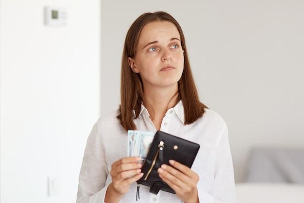 Внутренний снимок грустной расстроенной темноволосой женщины в белой рубашке повседневного стиля, держащей в руках бумажник с деньгами и смотрящей в сторону, выражающей печаль, у которой недостаточно денег для покупок.