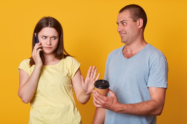 悲しい女性の室内でのショットは、男が動揺して表情を見せ、持ち帰り用のコーヒーを提供し、表情を動揺させ、携帯電話で会話し、黄色のスタジオの壁に立ち向かい、結婚している人はさりげなく着ています。