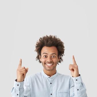 Снимок в помещении довольного счастливого афроамериканца с кудрявыми волосами, с широкой сияющей улыбкой и указательными пальцами вверх.