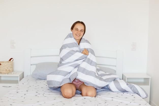 Крытый снимок удовлетворенной женщины, завернутой в серо-белое полосатое одеяло, сидящей на кровати в светлой спальне, смотрящей в камеру со счастливым выражением лица и зубастой улыбкой.