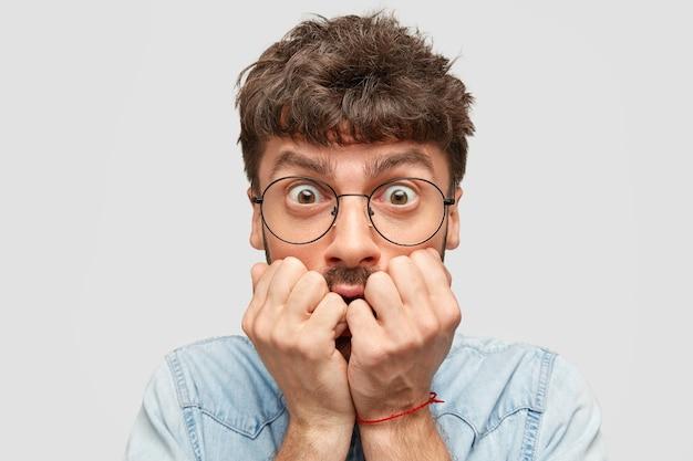 怖がっている神経質な男の学生の屋内ショットは、指の爪を噛み、恐怖で見つめ、黒髪をしています