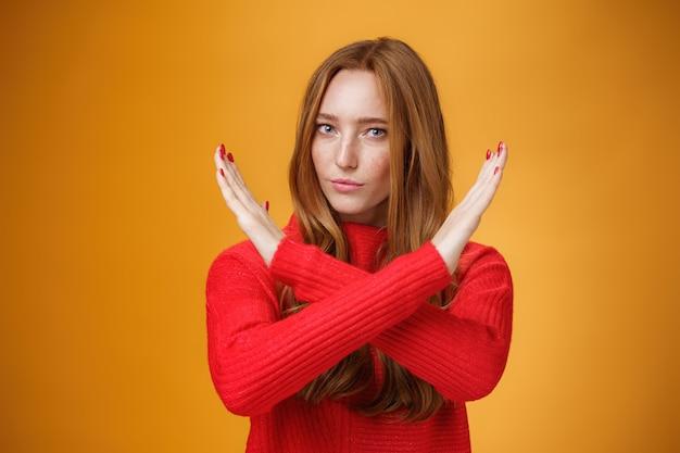 赤い髪とそばかすが腕を組んでいる自信のある魅力的な強力な女性の屋内ショットは禁止されており、禁止ジェスチャーはオレンジ色の壁の上に自信を持って立っている行動をします