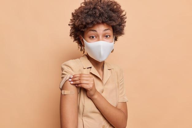 곱슬머리를 한 심각한 아프리카계 미국인 여성의 실내 사진은 코로나바이러스로부터 예방접종을 받았으며 베이지색 벽에 격리된 접착성 석고 일회용 안면 마스크로 예방접종을 받은 팔을 보여줍니다.