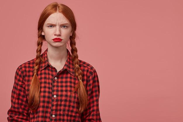 真面目で悲しい若い生姜の女性の屋内ショット。彼女の唇と眉毛を編み、混乱した表情でカメラに主演します。コピースペースでピンクの背景の上に分離