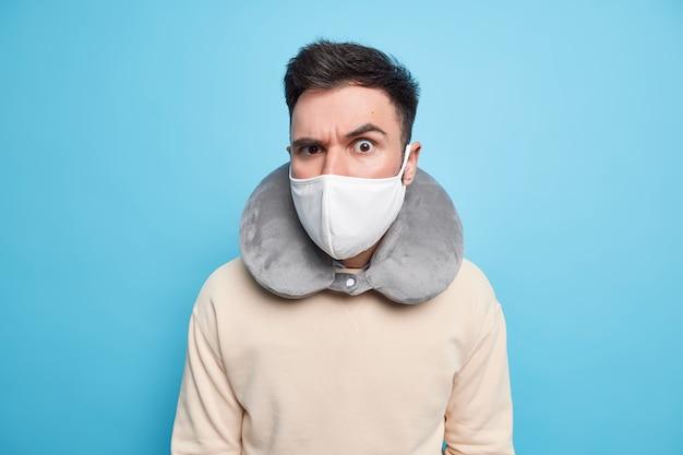 Снимок в помещении: серьезный внимательный мужчина в защитной маске от коронавируса, надутая шейная подушка для комфортного сна во время путешествия в транспорте, приподнимает бровь, внимательно смотрит,