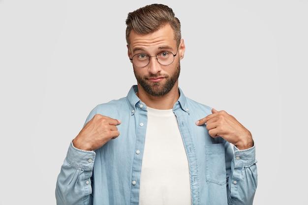 Снимок серьезного бородатого парня в помещении, позирующего на фоне белой стены