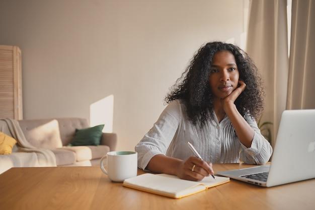 Снимок в помещении серьезной красивой молодой самозанятой женщины смешанной расы с волнистыми волосами, работающей удаленно с помощью ноутбука, сидящей в домашнем офисе с кружкой и дневником, записывающей и строящей планы на день