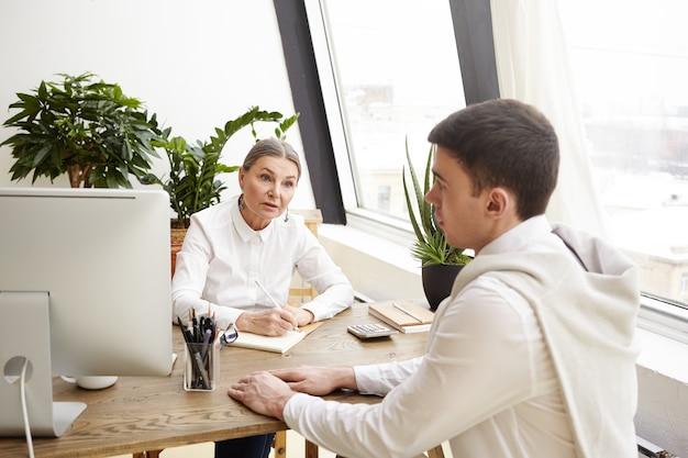 Снимок в помещении серьезной женщины-специалиста по кадрам среднего возраста в белой рубашке, сидящей на рабочем месте, проводящей собеседование с перспективным молодым кандидатом-мужчиной и делающей записи в своей записной книжке