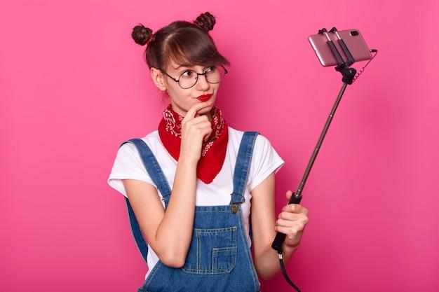 ピンクの上に孤立した、全体的にデニムを着て立っている深刻な思慮深い黒い髪のモデルの屋内ショット