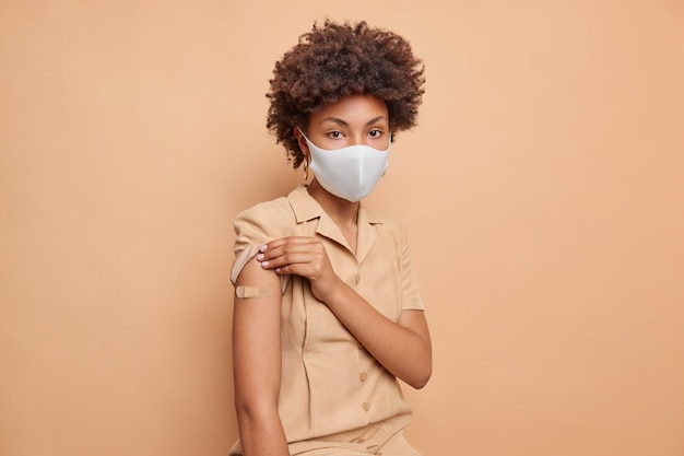 巻き毛の真面目な女性の屋内ショットは保護マスクを着用し、ドレスはワクチン接種が健康の世話をした後、漆喰の腕を示していますベージュのスタジオの壁に注射を隔離しました