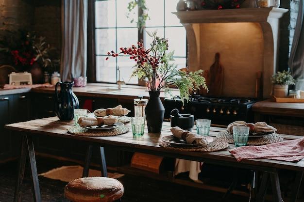 巻いたナプキンを添えたテーブルの屋内ショット。ディナータイムのコンセプト。テーブルセッティングの装飾。家庭の台所のインテリア。素朴なサービング