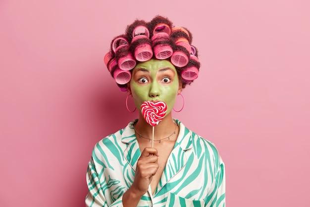 충격을받은 아프리카 계 미국인 여성의 실내 촬영은 완벽한 헤어 스타일을 만들기 위해 헤어 롤러를 적용하여 롤리팝으로 입을 덮고 녹색 영양 마스크를 만들어 분홍색 벽 위에 고립 된 미세한 선을 줄입니다.
