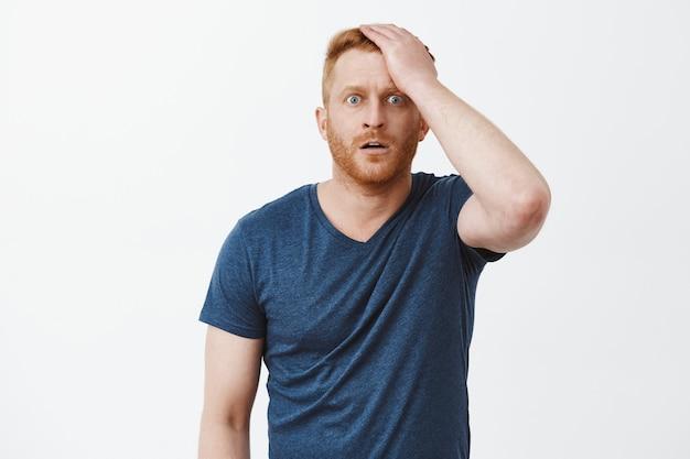 Снимок в помещении: шокированный и ошеломленный мужчина с рыжими волосами и щетиной, бьет себя по лбу и смотрит, потрясенный, сбитый с толку, стоящий в ступоре над серой стеной.