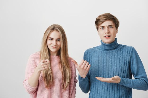 カラフルなセーターを着ているショックを受けた男性と渋面の女性の屋内撮影