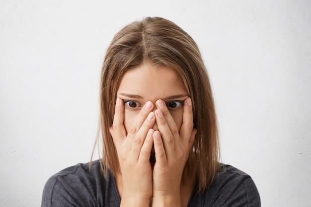 Снимок шокированной, напуганной или разочарованной молодой женщины, закрывающей лицо руками, с глазами, полными ужаса и паники.