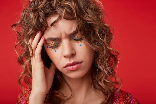 Снимок в помещении: больная кудрявая барышня с романтической прической и праздничным макияжем позирует с закрытыми глазами, держит голову рукой и хмурится из-за головной боли