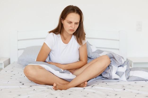 다리를 꼬고 침대에 앉아 있는 아픈 여성의 실내 사진, 흰색 캐주얼 티셔츠를 입고, 배를 만지고, 복통으로 고통받고, 찡그린 얼굴.