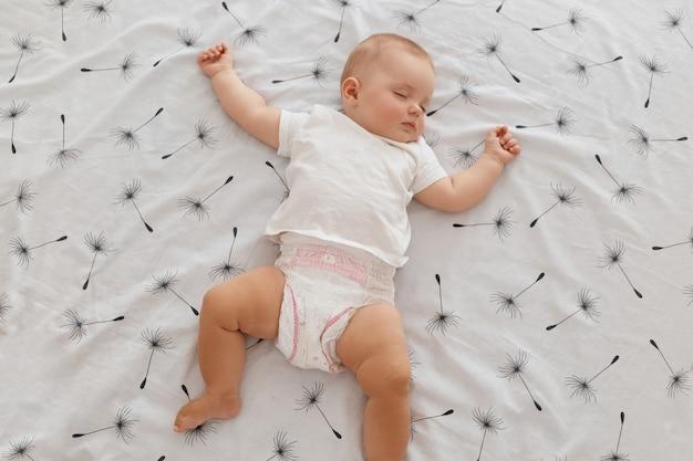 白いtシャツとおむつを身に着けて、腕を上げて目を閉じてベッドに横たわっている魅力的な女性の赤ちゃんを眠っている屋内ショット、幸せな子供時代。