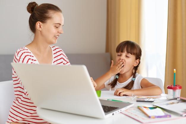 Снимок в помещении: сонный усталый школьник сидит за столом в гостиной, мать помогает дочери с уроками, позирует перед портативным компьютером, зевает ребенок.